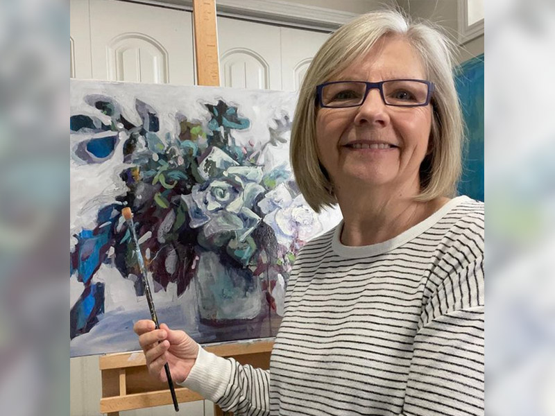 Judy Ruggles poses next to her painting of flowers in blue and grey tones