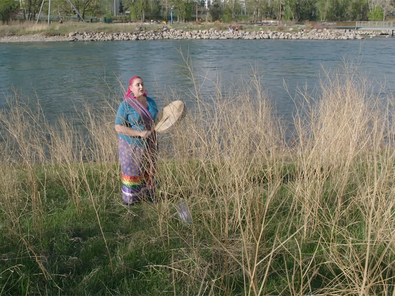 Chantal Chagnon drumming by the river