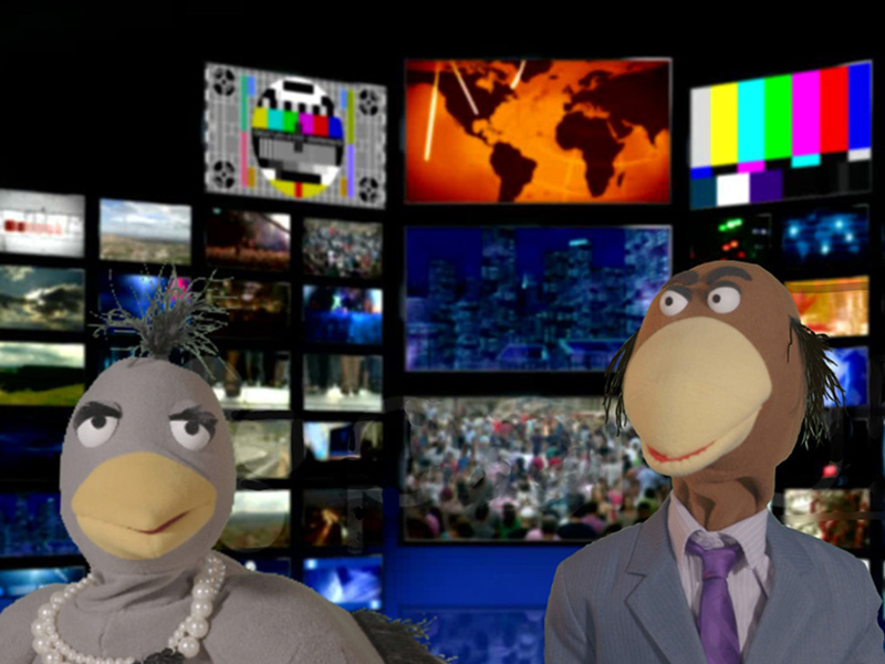 Two puppets in front of a wall of TVs promoting Green Fools News Drive-In