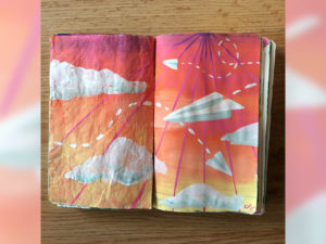 A sketchbook painted with colourful clouds and a paper airplane