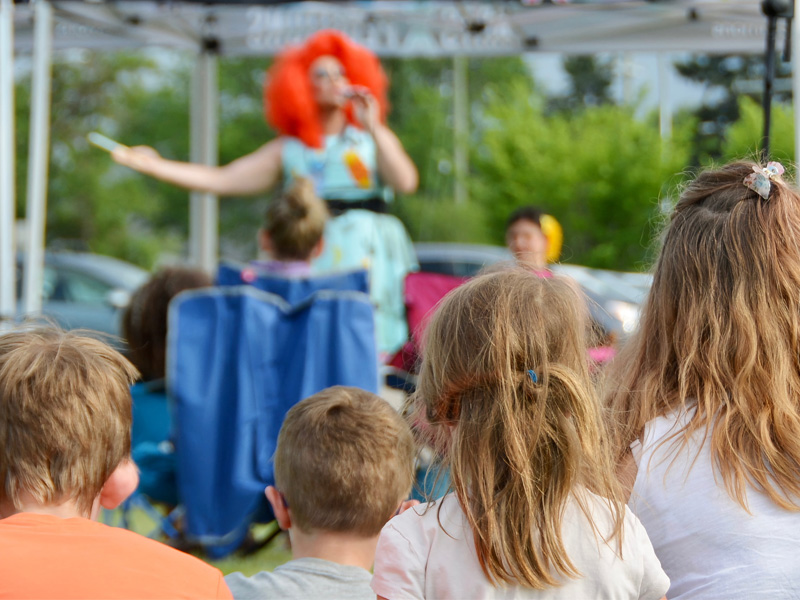 Children watch a performer at an outdoor pop-up ArtsXpeditions show