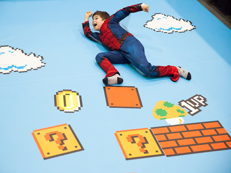 A child in a Spiderman costume playing on a Super Mario themed mat
