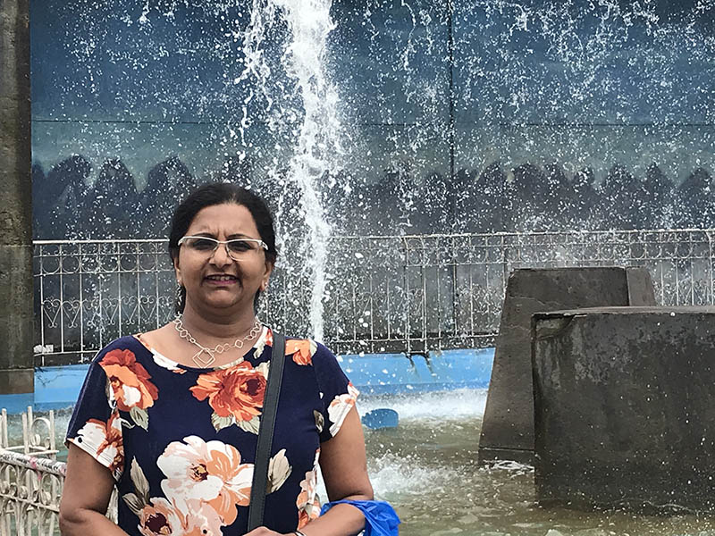 A photo of Pushkala Subramani in front of a fountain