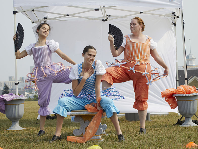 Three people in pastel, feminine costumes in front of a tent