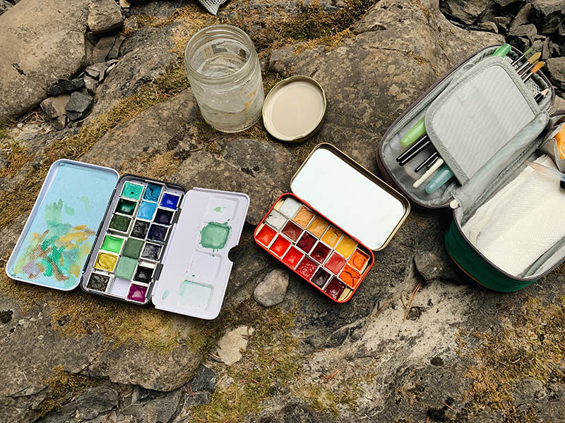A photo of painting tools sitting on rocks